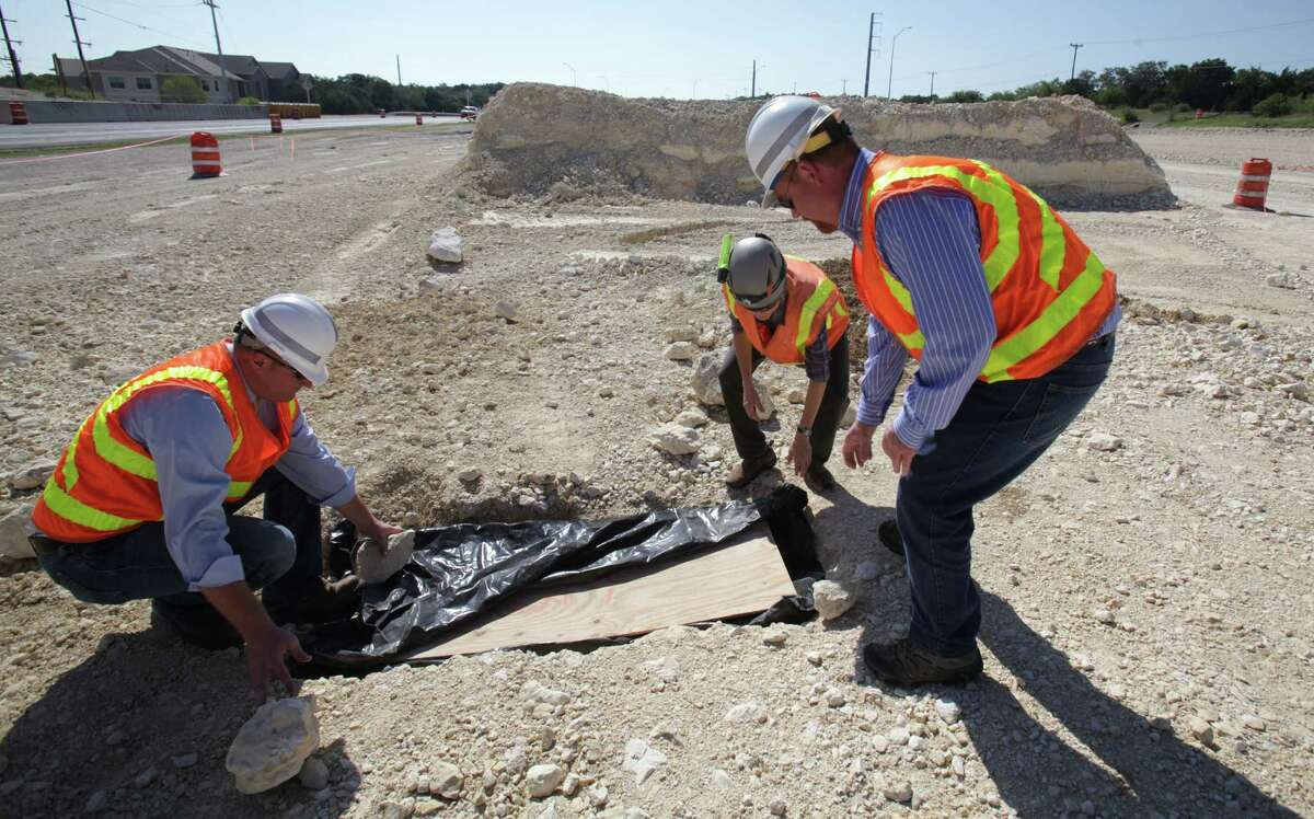 TxDOT workers Joshua Donat, left, Stirling Robertson, right, and Biologist Jean Krejca, center, inspect a small cave they found as construction workers were grading land along Texas 151 near Loop 1604 for an underpass. Endangered spiders were found in the small feature, halting construction work as Biologist study the rare spiders Friday, Sept. 7, 2012.
