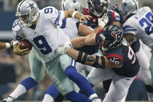 Cowboys quarterback Tony Romo escapes the grasp of Texans defensive end J.J. Watt before throwing a touchdown pass to Terrance Williams at AT&T Stadium. Photo: Karen Warren / Houston Chronicle / © 2014 Houston Chronicle