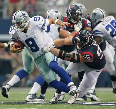 Dallas Cowboys quarterback Tony Romo (9) is nearly sacked by Houston Texans defensive end J.J. Watt (99) but was able to recover and and throw a touchdown during the third quarter of an NFL football game at AT&T Stadium, Sunday, Oct. 5, 2014, in Arlington. ( Karen Warren / Houston Chronicle  ) Photo: Houston Chronicle / © 2014 Houston Chronicle