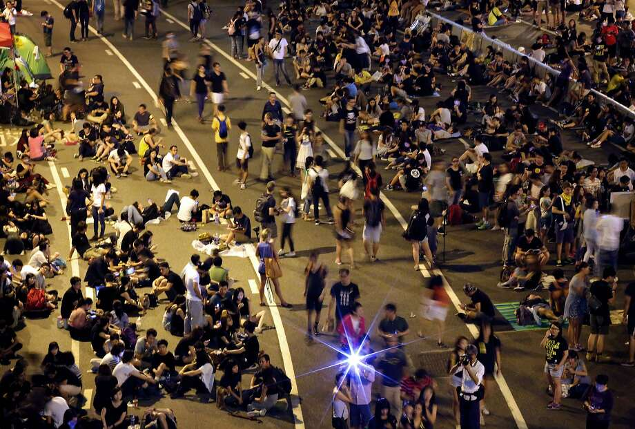 Student pro-democracy protesters continue to occupy the streets near government headquarters, Sunday, Oct. 5, 2014 in Hong Kong. In an apparent concession to authorities warning pro-democracy protesters to clear Hong Kong's streets by the beginning of the work week, students occupying the area outside city government headquarters agreed Sunday to remove some barricades that have blocked the building's entrance during the weeklong demonstrations. But it was not immediately clear how significant the move was and how much it would defuse the standoff, with many protesters vowing to stay in the area. (AP Photo/Wong Maye-E) Photo: Wong Maye-E, Associated Press