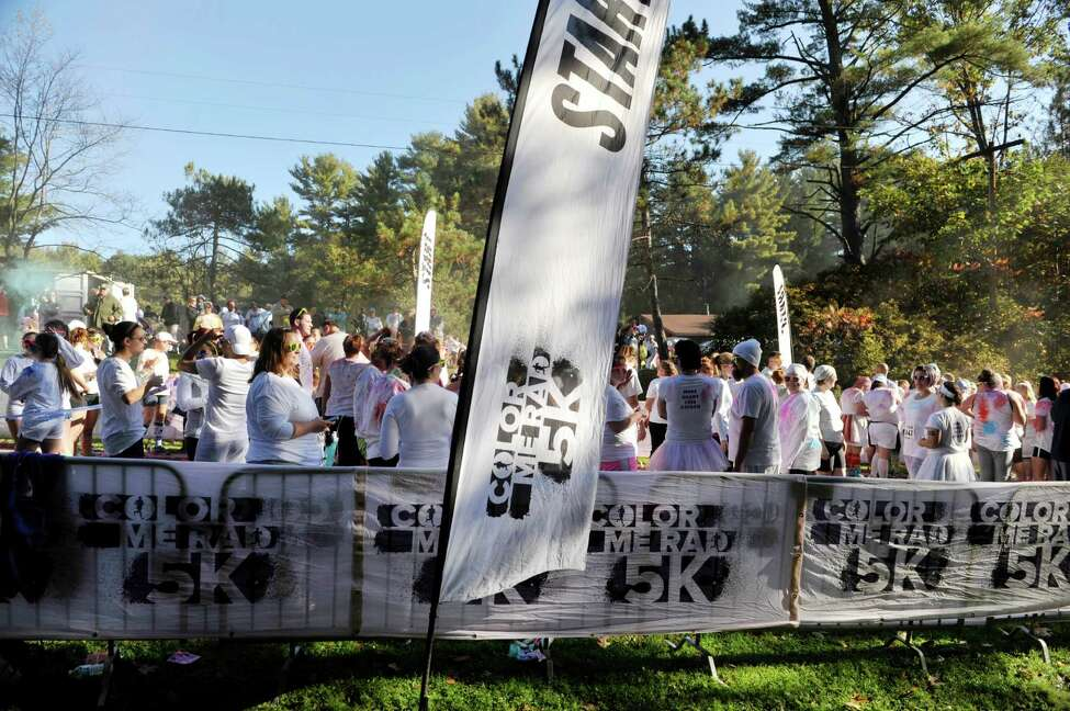 Runners taking part in the Color Me Rad run hang out in the starting chute before they run at the event at Saratoga Spa State Park on Sunday, Oct. 5, 2014, in Saratoga Springs, N.Y. The race has a charity partner, but it isn't well known. (Paul Buckowski / Times Union)