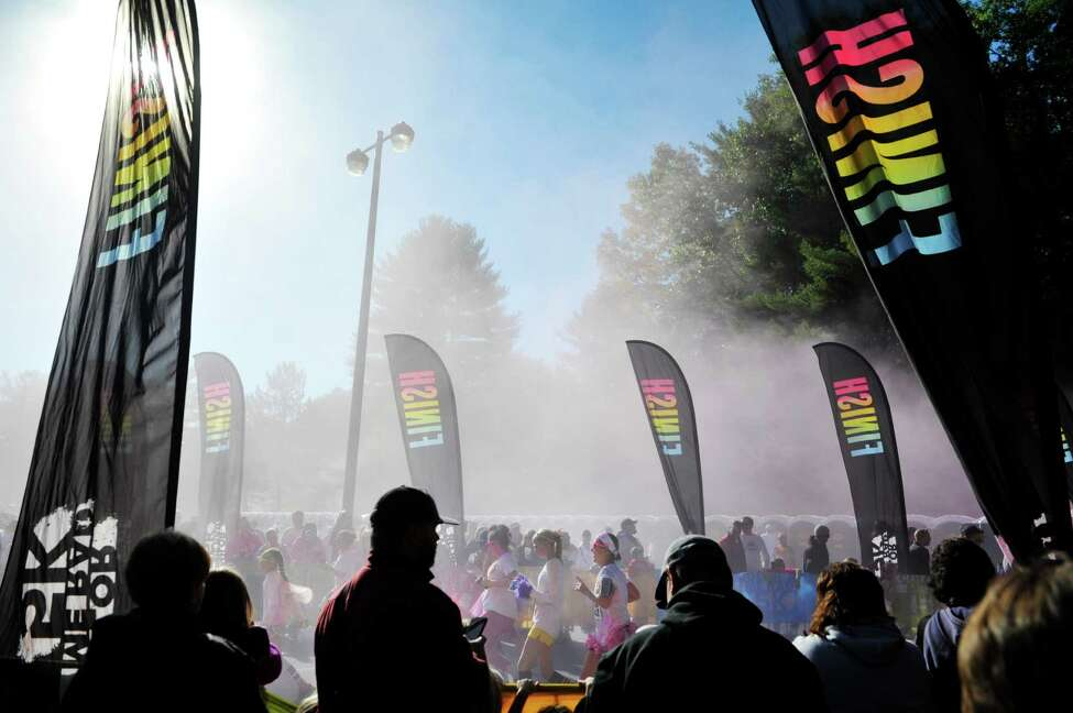 Runners taking part in the Color Me Rad run come through the finish line during the event at Saratoga Spa State Park on Sunday, Oct. 5, 2014, in Saratoga Springs, N.Y. Color Me Rad has a charity partner, Special Olympics of New York, but it's a for-profit event. (Paul Buckowski / Times Union)