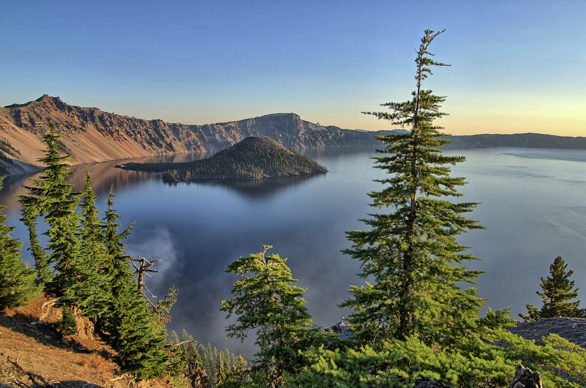 Dawn may be the best time to view Crater Lake, when the water is like glass. The island in the background is Wizard Island, formed by a cinder cone.