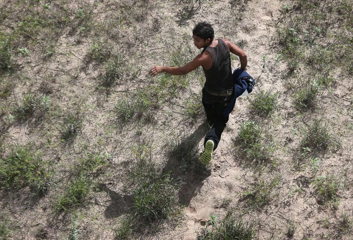 A would be immigrant flees while being chased by federal agents from U.S. Customs and Border Protection on September 9, 2014 near Falfurrias, Texas. Thousands of migrants continue to cross illegally from Mexico into the United States, and Texas' Rio Grande Valley has more traffic than any other sector of the U.S.-Mexico border. (Photo by John Moore/Getty Images)