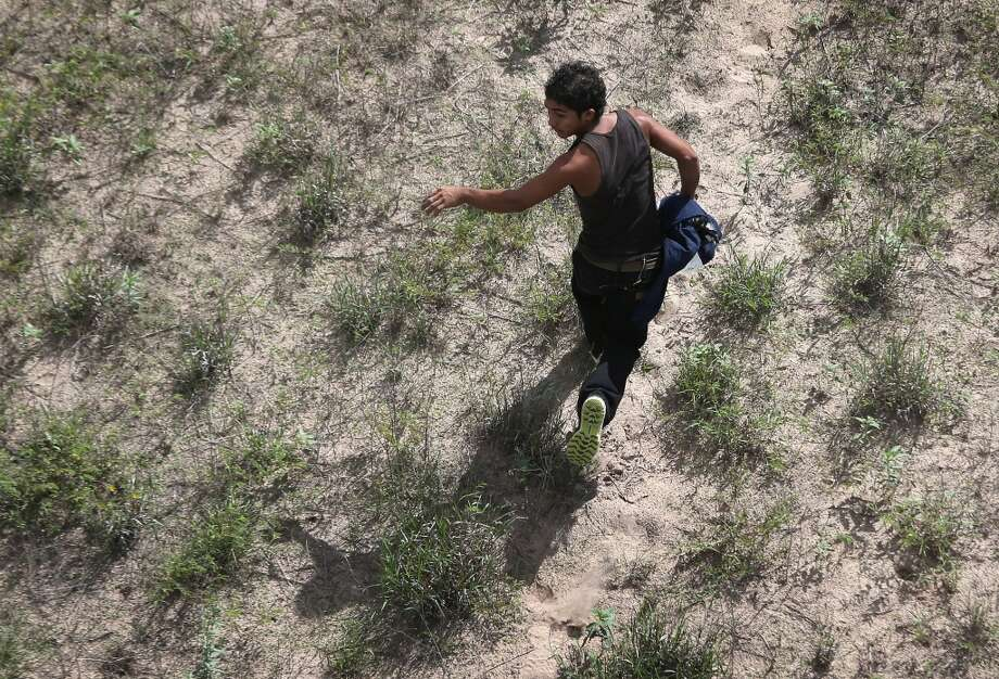 A would be immigrant flees while being chased by federal agents from U.S. Customs and Border Protection on September 9, 2014 near Falfurrias, Texas. Thousands of migrants continue to cross illegally from Mexico into the United States, and Texas' Rio Grande Valley has more traffic than any other sector of the U.S.-Mexico border.  (Photo by John Moore/Getty Images) Photo: John Moore, Getty Images