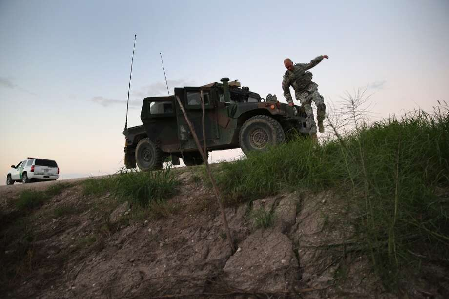 Texas National Guard troops watch for illegal immigrant crossings near the Rio Grande River at the U.S.-Mexico border on September 8, 2014 near McAllen, Texas. Thousands of undocumented immigrants continue to cross illegally into the United States, although the numbers are down from a springtime high. Texas' Rio Grande Valley area is the busiest sector for illegal border crossings, especially for Central Americans, into the U.S.  (Photo by John Moore/Getty Images) Photo: John Moore, Getty Images