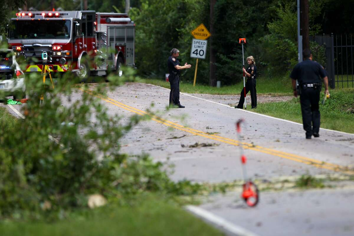 Harris County Sheriff conduct an investigation where a fallen tree struck an SUV causing the driver to drive off the road along 4722 Treaschwig Road in Spring. | Gary Coronado, Houston Chronicle