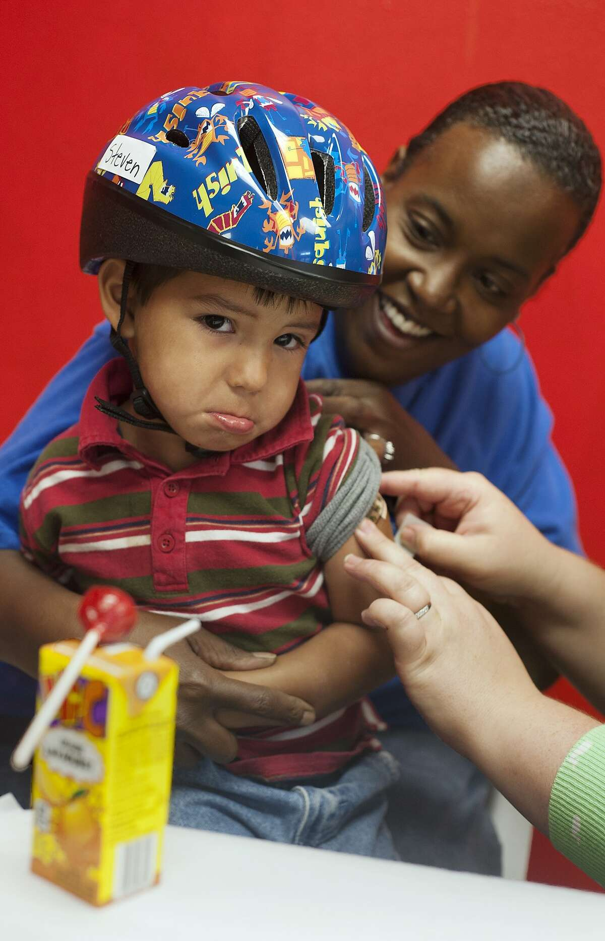 Should have put it on my arm instead of my head: Despite getting a lollipop, juice and a free bicycle helmet, 3-year-old preschooler Steven Barron can only pout after receiving a vaccination shot at Tyler Day Nursery in Tyler, Texas.