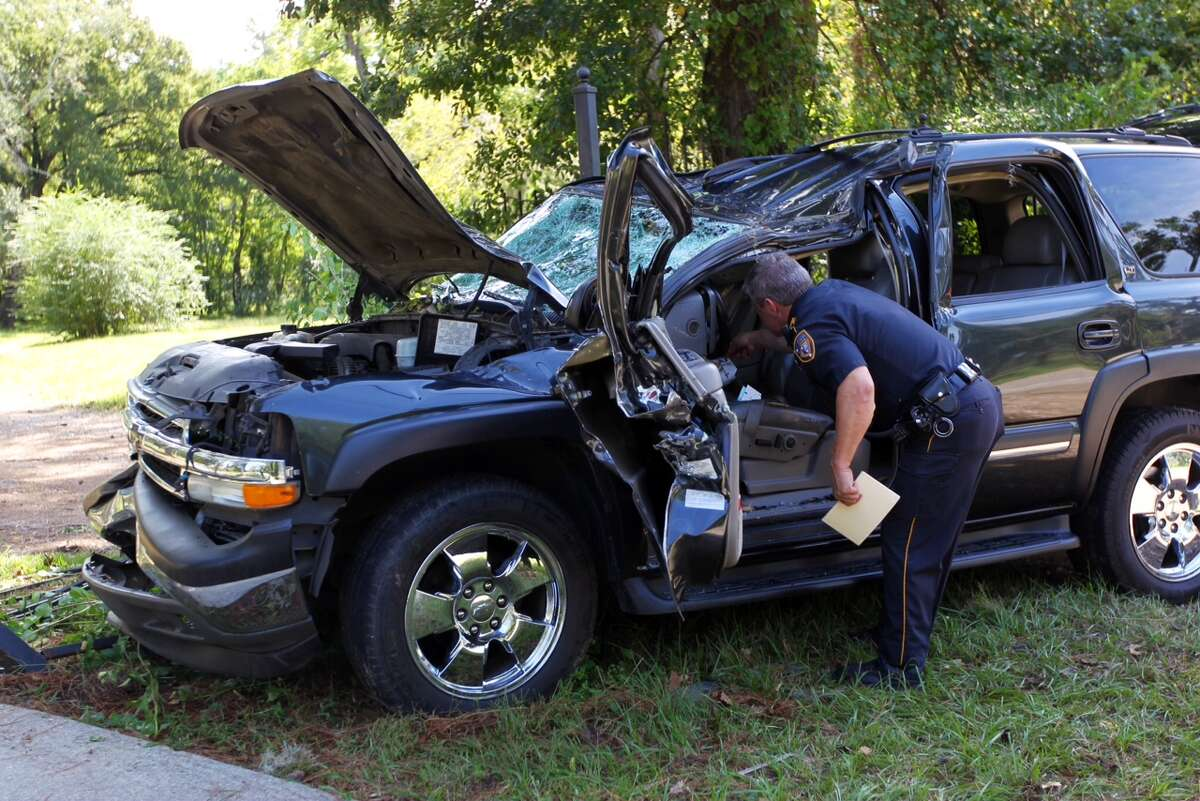 Harris County Sheriff's deputies conduct an investigation where a fallen tree struck an SUV causing the driver to drive off the road along 4722 Treaschwig Road in Spring. One person died and thousands lost power as heavy thunderstorms raked the Houston region Monday, Oct. 6, 2014.