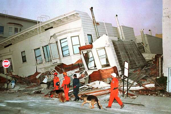Rescue dogs are brought into position to begin searches of destroyed houses in the Marine District of San Francisco, Ca., Wednesday morning after a strong earthquake caused widespread damage, Oct. 18, 1989. (AP Photo/Eric Risberg)