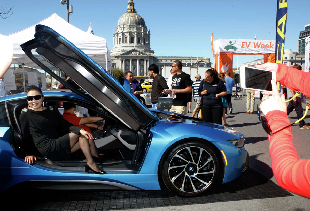 Tourists take pictures in the 2014 BMW i8, an electric sports car seen at the annual Charge Across Town in the plaza between the SF main library and Asian museum in San Francisco, Calif., on Monday, October 6, 2014.