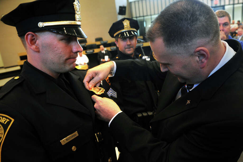 Bridgeport Police Sergeant Bob Magnuson, right, pins the shield onto new Sergeant Trevor Niestemski during a promotional cememony in Bridgeport, Conn. Sept. 4, 2014. Photo: Ned Gerard / Connecticut Post
