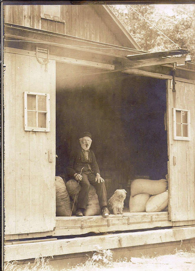 Charles Mathews sits in the doorway of the Mathews Feed and Flour Mill, which served families in northwest Stamford, northeast Greenwich and Bedford, N.Y., from the 1850s to the early 1900s. The story of that complex of mills, known as Newman Mills, is one of several told at a new exhibition at the Stamford Museum and Nature Center in Stamford, Conn., through Nov. 4, 2014. Photo: Contributed Photo / Stamford Advocate Contributed photo