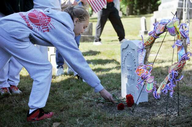 A student identified only as MacKenzie, a seventh grader from Holy Spirit School, places a flower at the head stone during a Civil War veteran memorial installation at the grave of James O Connell at the St. Agnes Cemetery on Monday, Oct. 6, 2014, in Menands, N.Y.  (Paul Buckowski / Times Union) Photo: Paul Buckowski / 00028889A