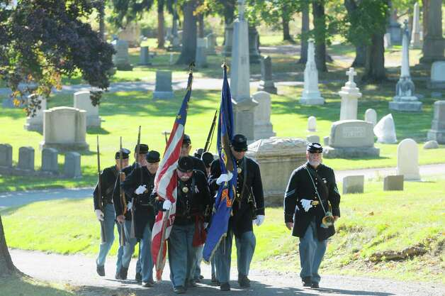 Re-enactors with the 125th New York Regimental Association, walk up to take part in a Civil War veteran memorial installation at the grave of James O Connell at the St. Agnes Cemetery on Monday, Oct. 6, 2014, in Menands, N.Y. (Paul Buckowski / Times Union) Photo: Paul Buckowski / 00028889A