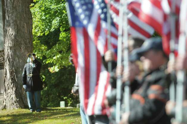 Re-enactor Rich Talay from Athens with the 125th New York Regimental Association plays Taps as he takes part in a Civil War veteran memorial installation at the grave of James O Connell at the St. Agnes Cemetery on Monday, Oct. 6, 2014, in Menands, N.Y.   (Paul Buckowski / Times Union) Photo: Paul Buckowski / 00028889A