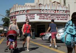 People walk by The Grand Lake Theater's marquee, which is on the intersection of lakeside st. and grand ave., which has a message endorsing Joe Tuman and takes aim at his rivals who are also running for Mayor in Oakland, Calif., on Saturday October 4, 2014.