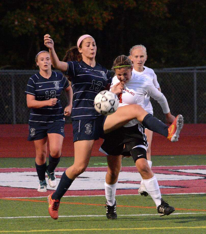 Immaculate High Schools Paige Davis fights for possession of the ball against Pomperaug High Schools Lauren Piro during a game at Pomperaug on Monday, October 6, 2014. Photo: Lisa Weir / The News-Times Freelance