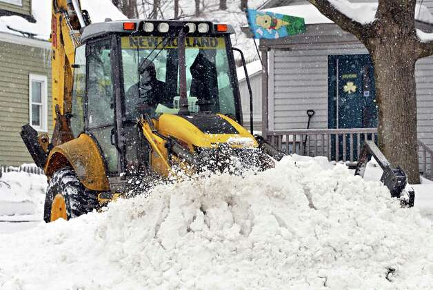 City crews use heavy equipment to clear snow from the corner of 9th Ave. and 112th Street Tuesday Feb. 18, 2014, in Troy, N.Y.  (John Carl D'Annibale / Times Union) Photo: John Carl D'Annibale / 00025810A