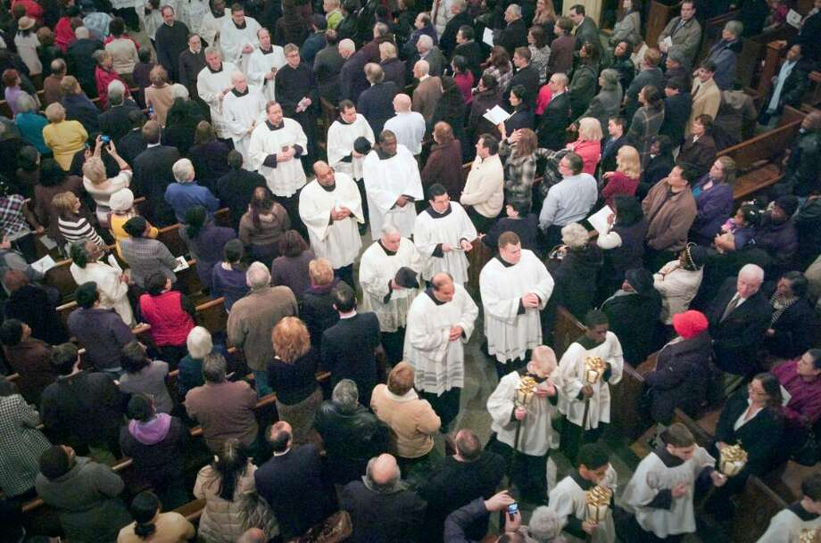 Priests process out of the church during the inauguration ceremonies for the Basilica of St. John the Evangelist in downtown Stamford, Conn. on Monday, Feb. 22, 2010. The church was officially designated by Pope Benedict XVI as a minor basilica, making it the second minor basilica in the state after the Basilica of the Immaculate Conception in Waterbury. Photo: Chris Preovolos / Stamford Advocate