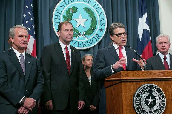 Texas Gov. Rick Perry, center, flanked by Dr. Kyle Janek, State Sen. Charles Schwertner, Dr. Tammy Beckham, backgroung, and Dr. Brett Giroir, left to right, announces the Texas Task Force on Infectious Disease Preparedness and Response during a news conference held at the State Capitol in Austin, Texas, on Monday, Oct. 6, 2014. Perry says he's creating the state task force to ensure Texas appropriately responds to infectious diseases like the Ebola virus. (AP Photo/Austin American-Statesman, Rodolfo Gonzalez)