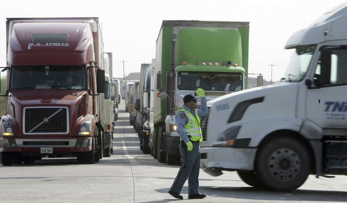 A police officer directs trucks in Laredo. Texas led the U.S. in exports last year, and Mexico was its top trading partner, taking 36.1 percent of those sales.