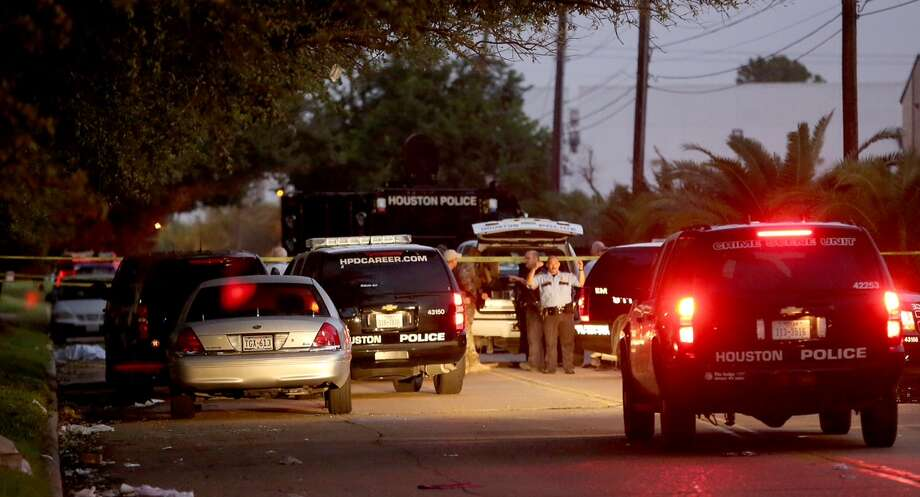 Police and SWAT crews work a shooting scene in the 5900 block of Bonhomne on Tuesday, Oct. 7, 2014. SWAT officers shot and killed a man who had been holding his estranged wife captive for hours. Photo: Thomas B. Shea, Thomas B. Shea / For The Houston Chronicle / © 2014 Thomas B. Shea