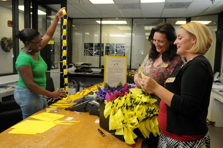 Eboni Washington, left, case manager at the Family Violence Center of Northwest Assistance Ministries; director Sheryl Johnson; and Melanie Jackman, youth educator, work on flags for a domestic violence memorial garden. Photo: Jerry Baker, Freelance