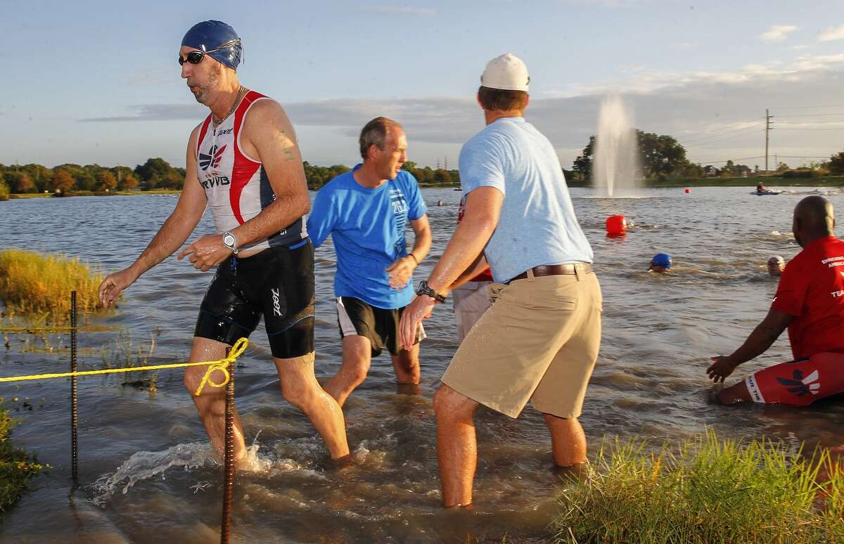 David Thurman of Team RWB gets help out of the water after the swimming portion of the Katy Triathlon.