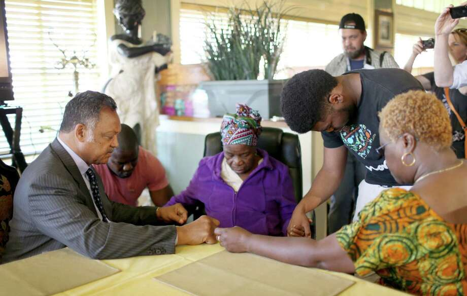 Rev. Jesse Jackson (L) prays with Nowai korkoyah (3nd L), the mother of Ebola patient Thomas Eric Duncan, as well as his nephew's, Josephus Weeks (2nd L), and Josephus Weeks jr. (2nd R) and sister, Mai Wureh, (R) before they spoke to the media at the South Dallas Cafe on October 7, 2014 in Dallas, Texas.  Rev. Jesse Jackson was visiting Dallas to show support of Ebola patient Thomas Eric Duncan and his family. Photo: Joe Raedle, Getty Images / 2014 Getty Images