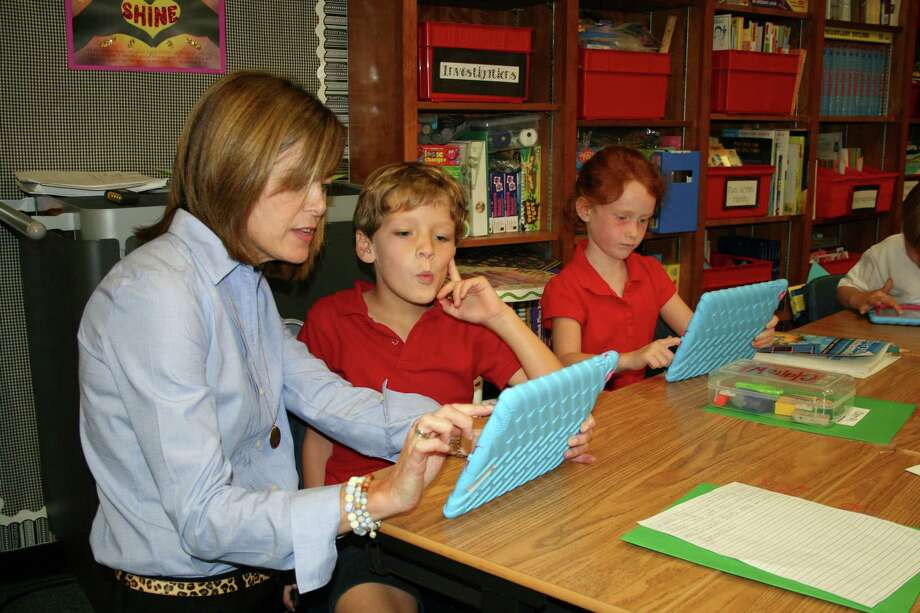 Bennett Cooper and Claire Whitehead, students at River Oaks Baptist School watch as Christi DeSpain shows how to use some of the great educational apps on the iPads that students use in class. Photo: River Oaks Baptist School