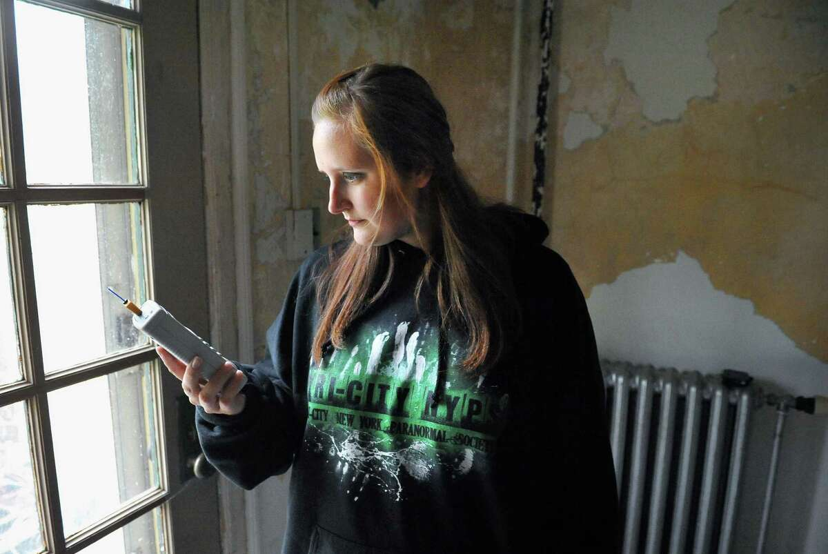 Paranormal investigator Samantha Brierley of the Tri-City New York Paranormal Society checks EMF and vibration readings with a Mel Meter in the Shaker Heritage Society Bretheren's workshop Saturday Oct. 4, 2014, in Colonie, NY. (John Carl D'Annibale / Times Union)