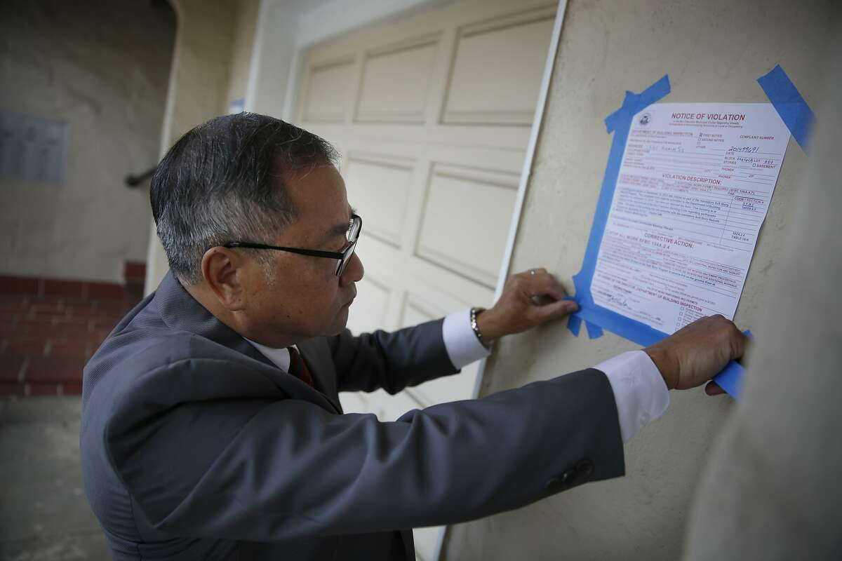 Tom Hui, director of Department of Building Inspection, added some tape to secure a Notice of Violation on a non-compliant soft story building on Tuesday, October 7, 2014 in San Francisco, Calif.