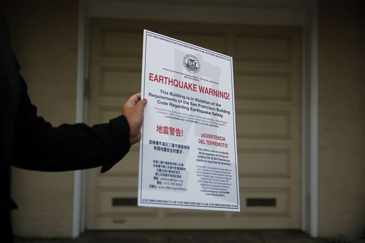 Lily Madjus, communications director Department of Building Inspection, holds a earthquake safety placard before it is secured on a non-compliant soft story building on Tuesday, October 7, 2014 in San Francisco, Calif.