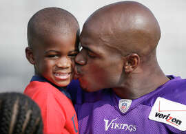 Minnesota Vikings running back Adrian Peterson gives one of his children, son Adrian Jr. a kiss after an NFL football training camp practice.