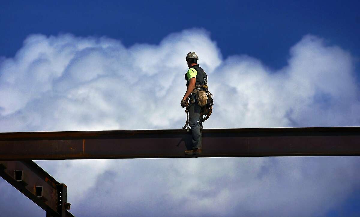 The view from his 'office': A steel worker balances on a beam at the construction site of The Learning Commons building at Marywood University in Scranton, Pa.