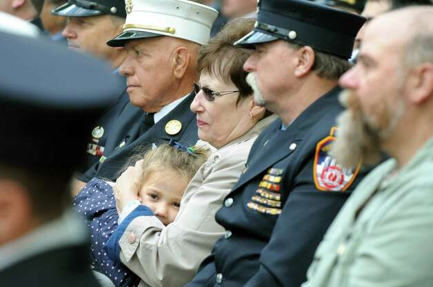 "Barbara DiBernardo, center, holds her granddaughter Gabriella Ingoglia, 3, as they listen to ""The Firefighters' Creed"" during the New York State Fallen Firefighters Memorial Ceremony on Tuesday, Oct. 7, 2014, at the Empire State Plaza in Albany, N.Y. DiBernardo lost her son, Lt. Joseph DiBernardo, who was with the New York City Fire Department. (Cindy Schultz / Times Union) Photo: Cindy Schultz / 00028598A"