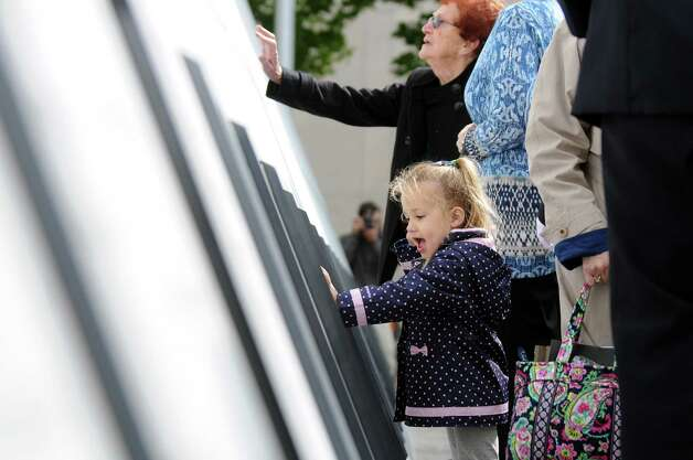 Gabriella Ingoglia, 3, center, touches the wall of names following the New York State Fallen Firefighters Memorial Ceremony on Tuesday, Oct. 7, 2014, at the Empire State Plaza in Albany, N.Y. The child lost her uncle, Lt. Joseph DiBernardo, who was with the New York City Fire Department. (Cindy Schultz / Times Union) Photo: Cindy Schultz / 00028598A
