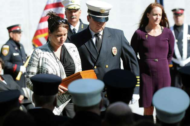 Christine Porcari, left, receives a flag in honor of her husband, Matthew Porcari, an Owego firefighter, during the New York State Fallen Firefighters Memorial Ceremony on Tuesday, Oct. 7, 2014, at the Empire State Plaza in Albany, N.Y. (Cindy Schultz / Times Union) Photo: Cindy Schultz / 00028598A