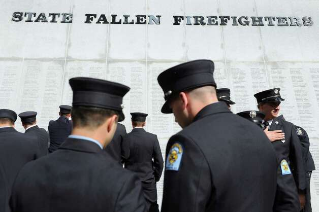 Firefighters gather to pay their respects at the monument following the New York State Fallen Firefighters Memorial Ceremony on Tuesday, Oct. 7, 2014, at the Empire State Plaza in Albany, N.Y. (Cindy Schultz / Times Union) Photo: Cindy Schultz / 00028598A