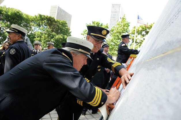 Chief Tim Shone of the Laurelton Fire Dept., center, and Commissioner Paul Groat trace the name of firefighter Arthur Sink following the New York State Fallen Firefighters Memorial Ceremony on Tuesday, Oct. 7, 2014, at the Empire State Plaza in Albany, N.Y. (Cindy Schultz / Times Union) Photo: Cindy Schultz / 00028598A