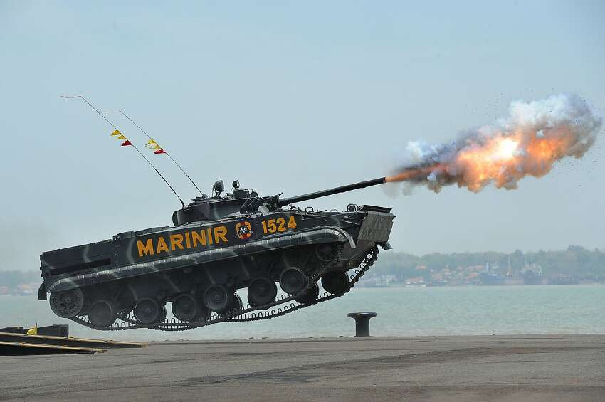 Meanwhile at the Armor X-Games ... An Indonesian Marine tank fires while making a flying leap during the 69th Republic of Indonesian Military Anniversary in Surabaya. This year's anniversary celebration is the biggest in the past decade with the army, navy, marines and air force all taking part.