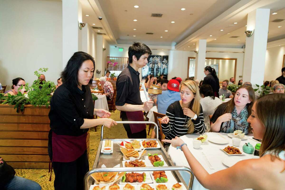 Anastasia Berg, Kara McBride and Terra Perrault (right) order dim sum items from Ann Chen at City View restaurant during brunch in San Francisco.