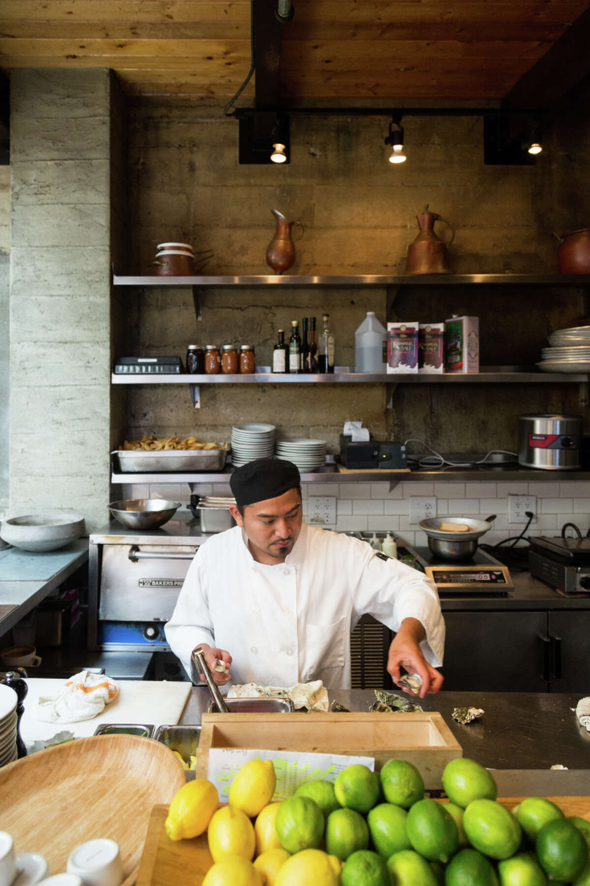 Roberto Medina shucks oysters during brunch at Foreign Cinema in San Francisco.