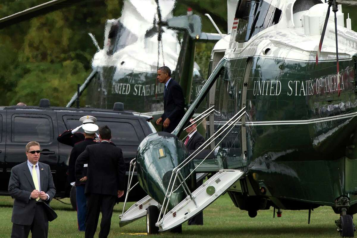 President Barack Obama walks off Marine One after arriving for a fundraiser, on Tuesday, Oct. 7, 2014, in Greenwich, Conn. Obama is traveling to New York and Connecticut for Democratic fundraisers.