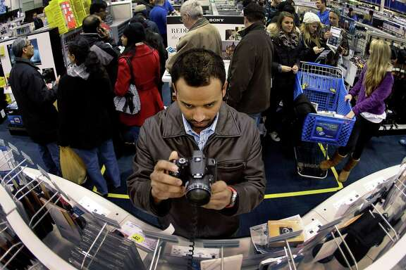 Ripan Bhowmik checks out cameras at a Best Buy in Overland Park, Kan., last November. Higher spending is expected this holiday season.