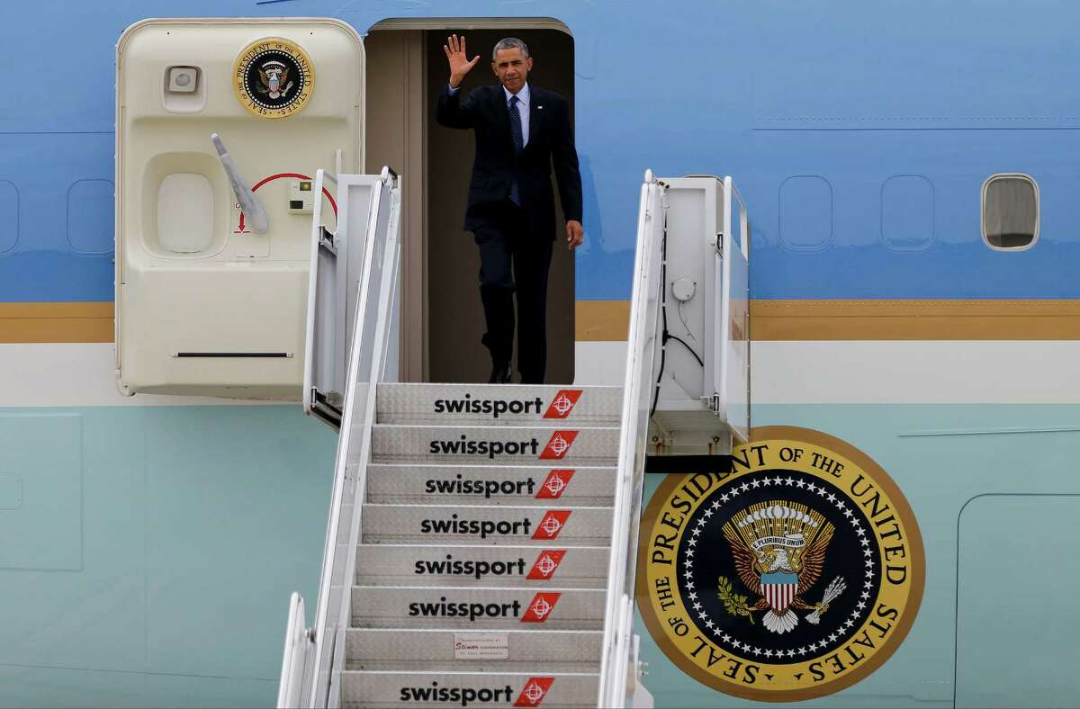President Barack Obama waves as he steps out of Air Force One upon arriving at JFK International Airport in New York, Tuesday, Oct. 7, 2014. The president is attending fundraisers in New York and Greenwich, Conn.