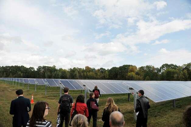 Skidmore College students, staff and guests tour the solar project during an event to unveil the college's large solar electric project on Tuesday, Oct. 7, 2014, in Greenfield Center, N.Y. The solar project consists of 6,950 ground-mounted solar panels over eight acres. The panels will generate 2.6 million kilowatt hours of electricity annually.  (Paul Buckowski / Times Union) Photo: Paul Buckowski / 00028888A