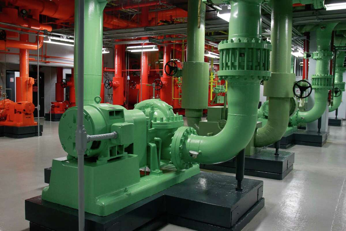 A condenser pump at 2 Houston Center helps save energy. A report calls for more financing options for green energy.