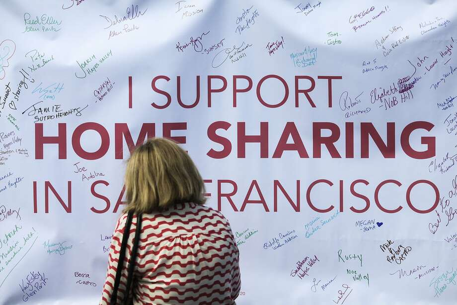 Sharon Cambell, an Airbnb host in San Francisco, signs a poster in support of home sharing at a rally held by Home Share SF, at Civic Center Plaza in San Francisco in October 2014. Photo: Sam Wolson, Special To The Chronicle